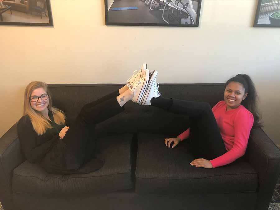 Two female coworkers on the couch showing off their white converse shoes